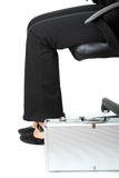 Suitcase at legs of business woman Stock Photo