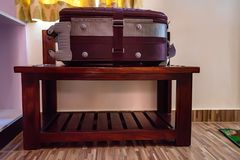 Suitcase lies on luggage stand in hotel. Close up purple travel suitcase with wheels lying on wooden stand in hotel Royalty Free Stock Image