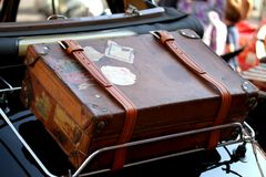 Suitcase in the luggage rack of vintage car. Very old suitcase in the luggage rack of vintage car before a trip Royalty Free Stock Image