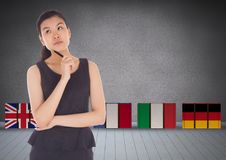 Suitcase with main language flags behind young woman thinking Stock Photography