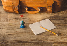 Suitcase, nootbook, pencil, flag on wooden planks. Aim, attainment, target, tourism, travel. At dawn. Hipster style. Top view with Stock Images