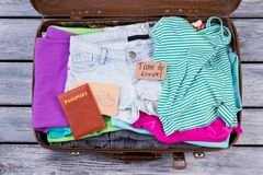 Suitcase packed with folded clothes and accessories. Top view, flat lay. Wooden desk surface Royalty Free Stock Photography
