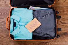 Suitcase packed with neatly folded clothes. Map and mail with stamps Royalty Free Stock Image