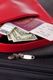 Suitcase Passport tickets and money. Suitcase with a red bag containing a passport with airline tickets, currency and baggage label. The tickets and labels are Stock Images