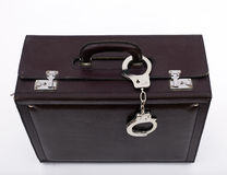 Suitcase from pinned closed metal handcuffs Stock Image