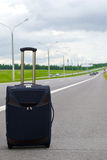 Suitcase on road. One suitcase on the road Stock Image