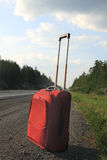 Suitcase on the road Royalty Free Stock Image