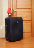 Suitcase and santa hat against a wooden door. Royalty Free Stock Image