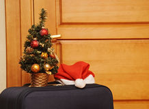 Suitcase and santa hat against a wooden door. Royalty Free Stock Photo