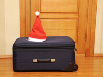 Suitcase and santa hat against a wooden door. Stock Photography
