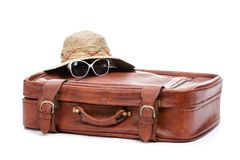 Suitcase and straw hat with glasses lying on it Royalty Free Stock Images