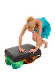Suitcase too full. Pretty blond woman trying to close her suitcase that is overflowing Stock Photo