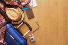 Suitcase and tourist stuff. On wooden background Stock Image