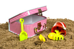 Suitcase and toys in the sand Royalty Free Stock Photography