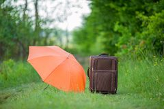 Suitcase with umbrella Stock Images