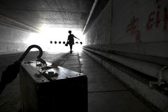 Suitcase and umbrella in an underpass stock images