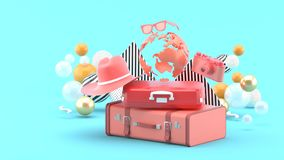 A suitcase under the globe surrounded by a camera and hat on an blue background royalty free illustration