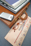 Suitcase With Financial Newspaper And PDA Royalty Free Stock Images