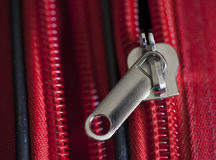 Suitcase Zip. A partly undone zip on a red suitcase Stock Photos
