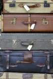Suitcases. Old antique brown, cream, blue and grey suitcases stacked on one another stock photos