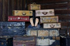 Suitcases and Feet. Human feet protruding out of a large stack of antique suitcases Royalty Free Stock Images