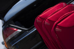 Suitcases in front of a trunk. Red suitcases waiting to be packed and ready for travel Royalty Free Stock Images
