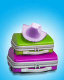 Suitcases with hat. Two bright suitcases with a female cowboy party hat in pink resting on top. Displayed against a bright blue background with clipping path Stock Images