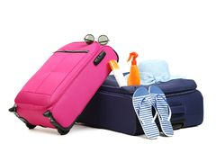 Suitcases with hat, flip flops and bottles. Isolated on white background stock photography