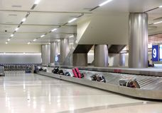 Suitcases on a luggage band at airport. Airport luggage claim with suitcases on the conveyor belt Royalty Free Stock Photo