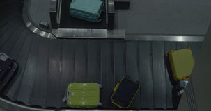 Suitcases on luggage conveyor at the airport. High angle shot of suitcases getting to the conveyor belt after arrival. Luggage at the airport baggage claim area stock video footage