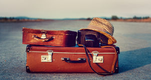 Suitcases on road. Vintage suitcases, photo camera and hat on road, concept of travel Stock Images