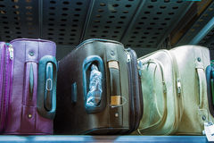 Suitcases on the shelf in the store. Sale of suitcases of different sizes and colors Stock Image