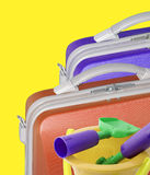 Suitcases and toys. Two bright colored suitcases on yellow isolated background with toy bucket and spade Stock Photography