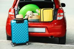 Suitcases and toys in car trunk royalty free stock images