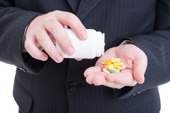Suited doctor hand holding pills Stock Photo