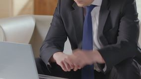 Suited employee finishing talking on phone, typing on laptop, sales manager