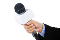 Suited hand holding microphone Royalty Free Stock Image