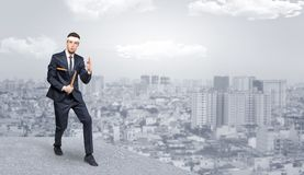 Suited karate man doing karate tricks on the top of a metropolitan city. Young suited karate trainer doing karate tricks on the top of a metropolitan city royalty free stock photo