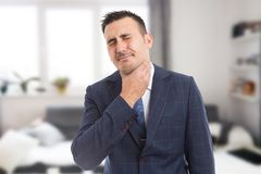 Suited male grabbing painful neck royalty free stock photo