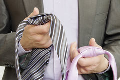 Suited man choosing ties. A suited man choosing between two ties which one to wear Royalty Free Stock Photo