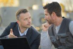 Suited man and workman looking at laptop outdoors. Laptop royalty free stock photography