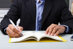 Suited man writing dairy Stock Image