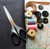 Suiting fabric, scissors, buttons and bobbins Royalty Free Stock Photo