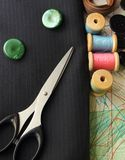 Suiting fabric, scissors, green buttons and bobbins Royalty Free Stock Photo