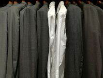 Suits for men in a shop and two white shirts Stock Photos