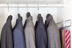 Suits and ties in wardrobe Stock Photography
