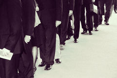 Suits waits in line. Retro black white with noise added Royalty Free Stock Photos