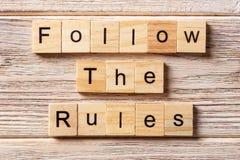 Suivez le mot de règles écrit sur le bloc en bois Suivez les règles textotent sur la table, concept Image libre de droits