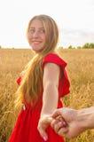 Suivez-moi, belles prises romantiques de jeune femme la main d'un homme dans un domaine de blé Image stock