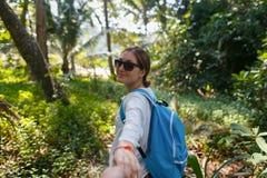 Suivez-moi concept de course Vue arrière de jeune femme avec le sac à dos découvrant dehors la jungle tenant la main du ` s d'ami Photographie stock libre de droits